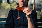 Woman Drinking Tea On Cemetery