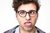 stock photo of dork  - Closeup portrait of a funny young man over gray background - JPG