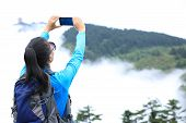 image of emei  - woman hiker taking photo at peak of emei mountain  - JPG