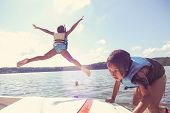 stock photo of boat  - Kids jumping off a boat into the lake - JPG