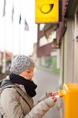 picture of postbox  - Young woman posting a letter - JPG