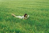 stock photo of wildflowers  - Beautiful girl lying on summer wildflower meadow and reading a book - JPG
