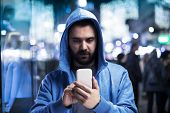 foto of boys night out  - Handsome young hipster with his smartphone outside in the night city - JPG