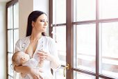 image of breastfeeding  - Mother breastfeeding her little baby girl in her arms - JPG
