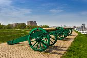 pic of cannon  - Ancient cannon at the earthen defensive shaft of an ancient fortress on a background of a modern city - JPG