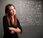 picture of anal  - Pretty young woman looking at stock market graphs and symbols - JPG