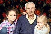 picture of granddaughters  - portrait of sitting senior man and granddaughters at home - JPG
