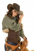 picture of cowgirls  - a cowgirl touching the brim of her hat holding onto her saddle - JPG