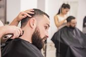 pic of clippers  - Hairdresser cuts hair with hair clipper on back of the head in hairdressing salon