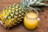 stock photo of juices  - Pineapple juice of pot on wooden table seen from above - JPG