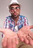 foto of hand kiss  - Handsome young man holding his hands in front while preparing his lips for a kiss - JPG