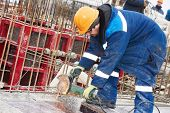 stock photo of millwright  - Construction builder worker with grinder machine cutting metal reinforcement rebar rods at building site - JPG