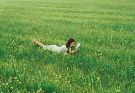 picture of wildflowers  - Beautiful girl lying on summer wildflower meadow and reading a book - JPG