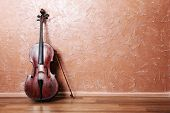 stock photo of cello  - Classical cello and bow on brown wall background - JPG