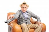 foto of angry man  - Angry senior man pressing buttons on a remote control seated in an armchair isolated on white background - JPG