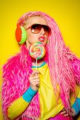 picture of dreadlock  - Attractive glamorous girl wearing ultra bright clothes and with pink dreadlocks eating lollipop - JPG