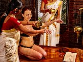 image of panchakarma  - Young woman having oil Ayurveda by two masseuse spa treatment - JPG