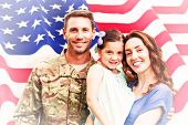 stock photo of reunited  - Soldier reunited with family against rippled us flag - JPG