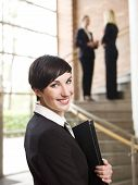 stock photo of frot  - Smiling businesswoman with a folder in frot of stairs - JPG