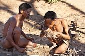 Namibia, Kalahari Desert, May 6, 2007: Two bushmen hunters has kindle a fire