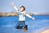 Happy jumping boy on beach
