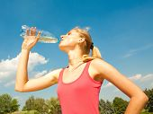 picture of drinking water  - Beautiful girl drinking water against blue sky - JPG