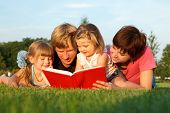 Sweet family reading a book on the green grass