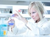 stock photo of retort  - Closeup of a female researcher holding up a test tube and a retort and carrying out some experiments - JPG