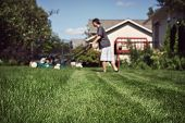 Adolescente cortar grama (extremamente rasa profundidade de campo, foco em primeiro plano)