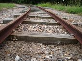 stock photo of train track  - Train tracks through a rural area on bright day - JPG
