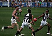 MELBOURNE - AUGUST 15: Collingwood's Alan Didak handballs to Leon Davis as Collingwood's midfield do