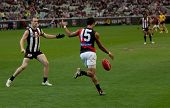 MELBOURNE - APRIL 25: Essendon's Courtney Dempsey kicks while Collinwood captain Nick Maxwell stands