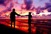 stock photo of love couple  - Silhouetted loving couple at sunset - JPG