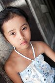 Young Philippine girl from impoverished neighborhood against wall.
