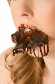 Close up of woman mouth full of melting chocolate pieces and covered by dripping syrup