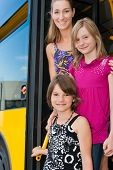 Mother and daughters looking out of a bus; they presumably like to get home