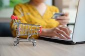 Close Up Mini Shopping Cart, Asian Woman Holding Credit Card And Using Laptop For Online Shopping Wh poster