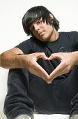 stock photo of emo-boy  - Sitting teenage boy making heart symbol with hands - JPG