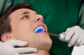 stock photo of uv-light  - Patient having dental checkup with ultraviolet light at dentist - JPG