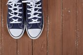 Clothes, Shoes And Accessories - Top View Fragment Closeup Pair Blue Gumshoes On A Wooden Background poster