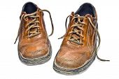 Old scuffed hiking boots isolated on a white background