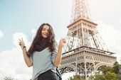 Young Attractive Happy Woman Showing Peace Gesture Eiffel Tower In Paris, France. Portrait Of Travel poster
