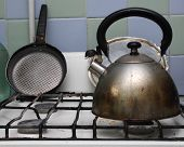 Dirty gas stove with teakettle and frying pan on it.