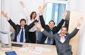 Joyful business team in office celebrating in office