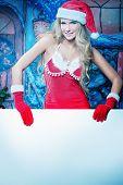 Постер, плакат: Сексуальная молодая женщина в Рождество одежды Холдинг белой доски на Рождество фон
