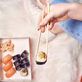 Japanese Sushi Set Nigiri And Sushi Rolls Served With Wasabi And Ginger, Girls Hands Holding Sushi poster