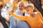 Active Seniors Taking Selfies Of Them Having Fun Outside In The Autumn Forest poster