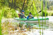 Kayaking on river in forest. Family on canoe. Active recreation and vacation poster
