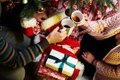Happy young couple giving present and drinking tea at home at Chrismas time. Christmas tree and gift poster