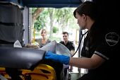 EMT worker listening to heart of elderly patient